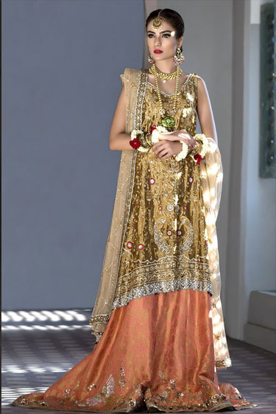 6ef15bd1f0 A bright golden long shirt with intricate detailing of thread embroidery  and til, zardozi work, a heavy net dupatta and peach jamawar lehnga with ...